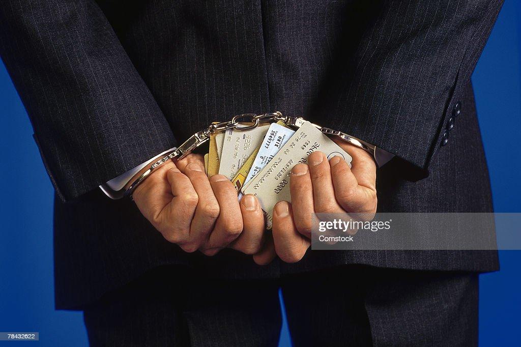 Handcuffed businessman holding credit cards : Stockfoto