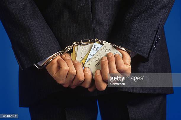 Handcuffed businessman holding credit cards