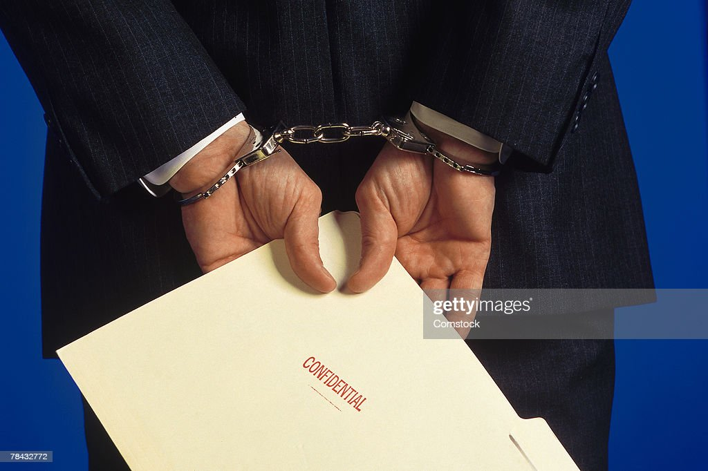 Handcuffed businessman holding folder marked confidential : Stockfoto