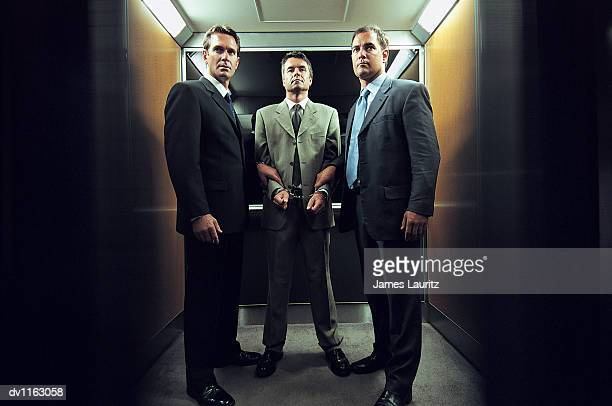 handcuffed businessman standing in an elevator between policemen dressed in suits - caught cheating stock pictures, royalty-free photos & images