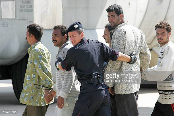 Handcuffed clandestine immigrants are escorted by Italian police 06 October 2004 at the Lampedusa civil airport, where they are due to board a...