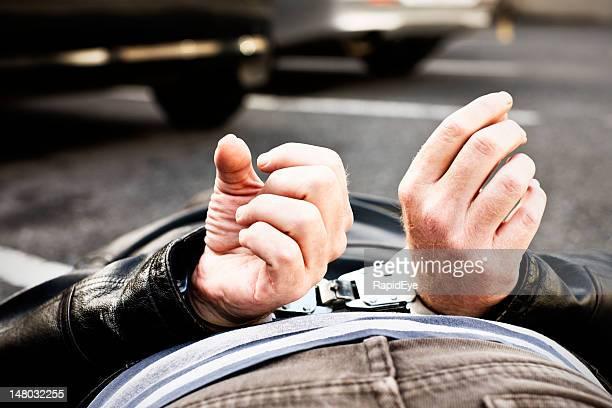 handcuffed 刑事体フェースダウンの駐車場 - 抑留者 ストックフォトと画像