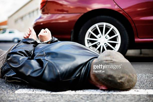 handcuffed man lies in road next to car - restraining stock photos and pictures