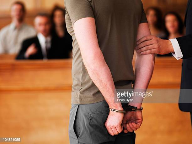 handcuffed man standing in courtroom - juror law stock pictures, royalty-free photos & images
