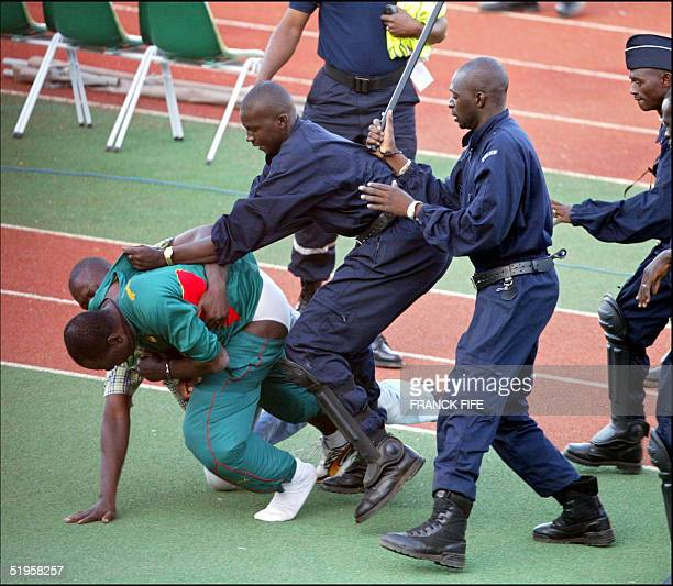 Handcuffed Thomas N'kono Assistant to Cameroon's German trainer Winfried Schaefer is dragged out 07 February 2002 in Bamako after about a dozen...