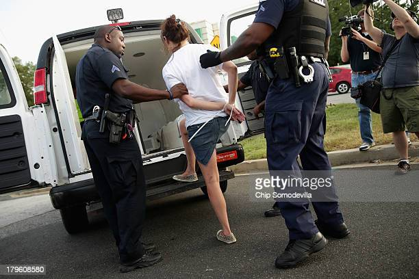 A handcuffed woman is loaded into a police van after she and hundreds of other demonstrators blocked traffic in a major intersection outside a...