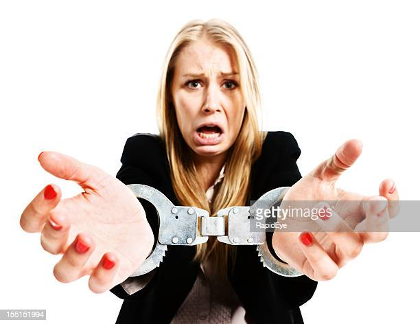 handcuffed young businesswoman protesting tearfully - prisoner stock pictures, royalty-free photos & images