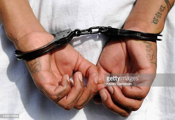 Handcuffs are seen on the hands of a twentyyear old 'Street Villains' gang member who was arrested by Los Angeles Police Department officers from the...