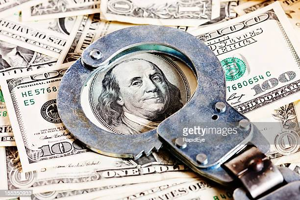 Handcuffs circle Benjamin Franklin in stack of dollars