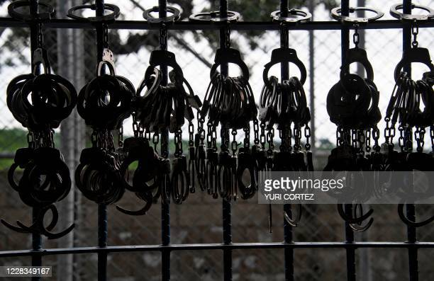 Handcuffs hang from a railing during a search operation at the maximum security prison in Izalco, Sonsonate, El Salvador, on September 4, 2020. -...