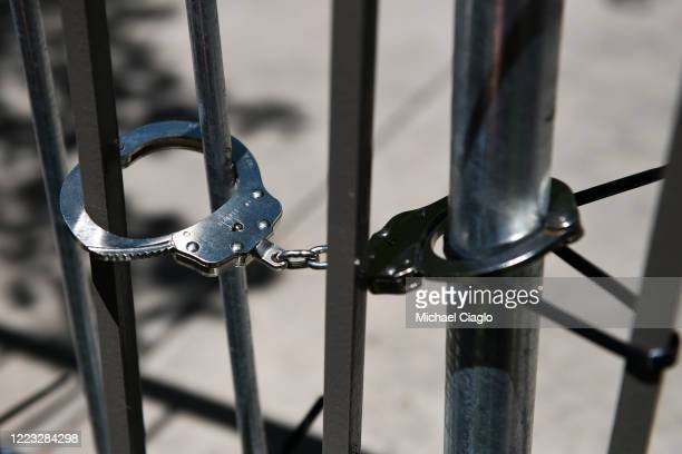 Handcuffs hold barricades together at a rally outside the Aurora Police Department Headquarters to demand justice for Elijah McClain on June 27, 2020...
