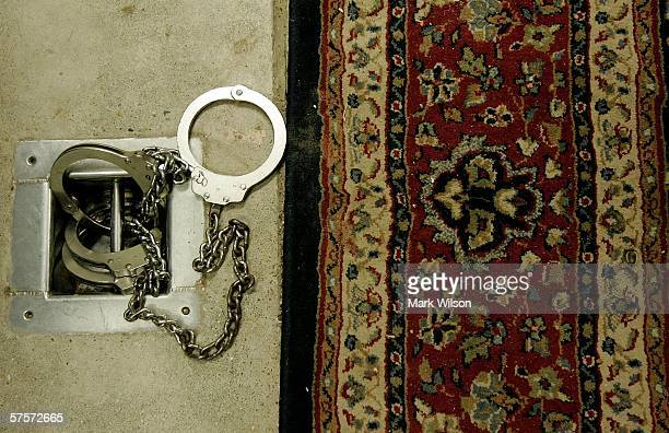 Handcuffs sit at the foot of a chair used for interrogation inside a cell in the maximum security Camp 5 at Camp Delta May 9, 2006 in Guantanamo Bay,...