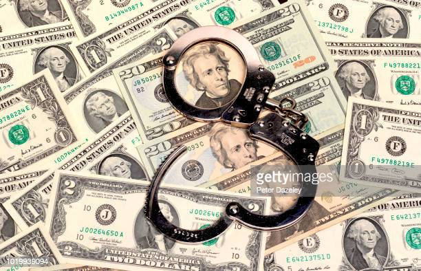 handcuffs sitting on top of us paper currency - money laundering stock pictures, royalty-free photos & images