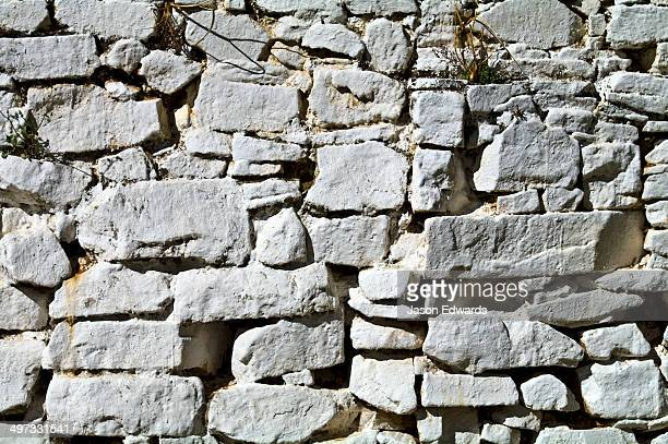 Hand-cut stones painted white form a wall in a Buddhist monastery.