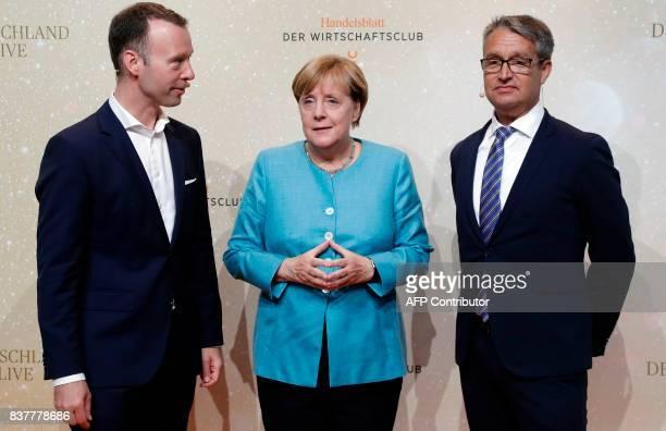 Handelsblatt chief editor Sven Afhueppe German Chancellor Angela Merkel and the Handelsblatt publisher Gabor Steingart pose for a photo prior to the...