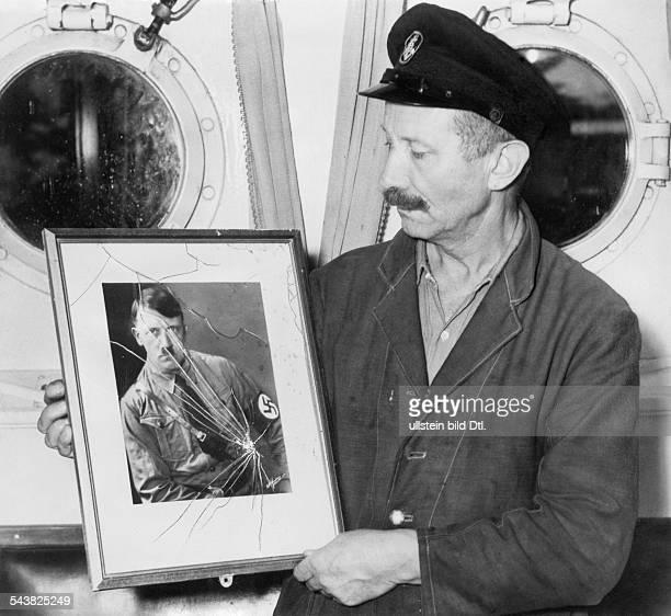 Handelsschiff 'Altmark' Ein Besatzungsmitglied der 'Altmark' präsentiert ein von den britischen Marinesoldaten zerstörtes Portrait von Adolf Hitler...