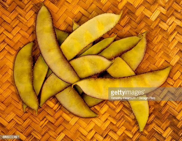 a handful of a tropical variety of peapods from a local farmers market rest on a woven mat on the big island - timothy hearsum stock pictures, royalty-free photos & images