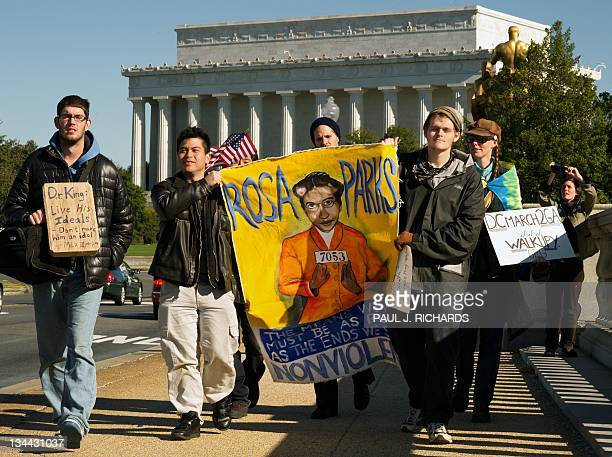 A handful of demonstrators from Occupy DC march over the Memorial Bridge with the Lincoln Memorial to the rear as they leave Washington DC and begin...
