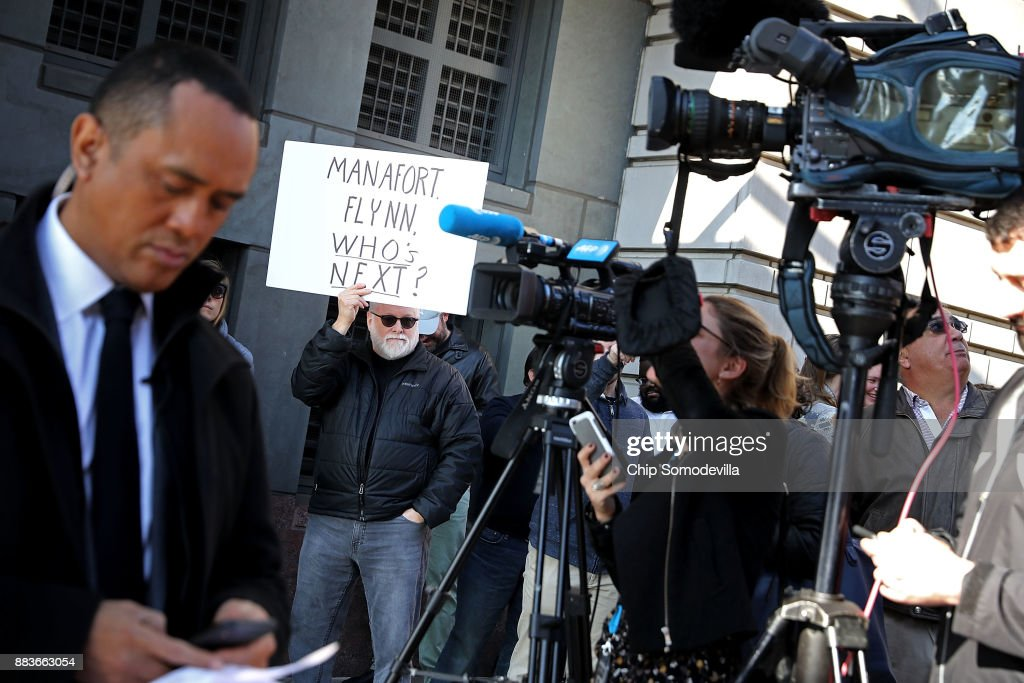 A handful of demonstrators held signs as they joined journalists outside the Prettyman Federal Courthouse where Michael Flynn, former national security advisor to President Donald Trump, had his plea hearing December 1, 2017 in Washington, DC. Special Counsel Robert Mueller charged Flynn with one count of making a false statement to the FBI.