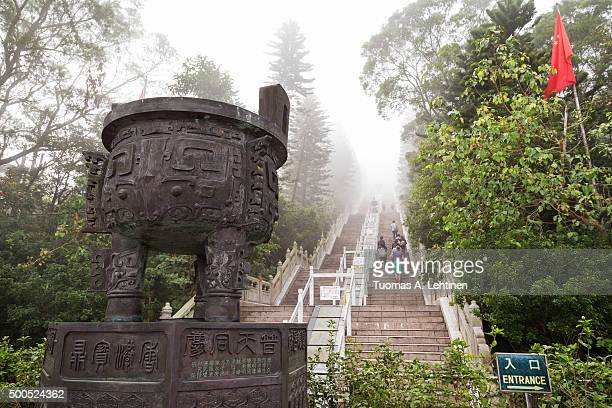 handful of people climbing long flight of stairs to the tian tan buddha or big buddha statue - temple of heaven stock pictures, royalty-free photos & images