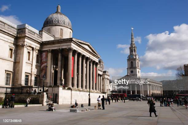 A handful of people walk across the almost deserted North Terrace of Trafalgar Square past the National Gallery in London England on March 16 2020...