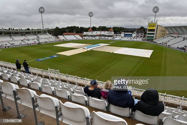 Handful of spectators sit in their seats as rain threatens to delay the start of play on the fifth day of the first Test match between England and...