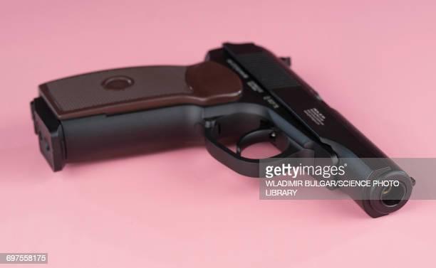 Handgun against a pink background