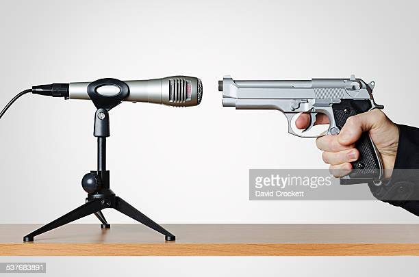 Handgun pointed at a microphone