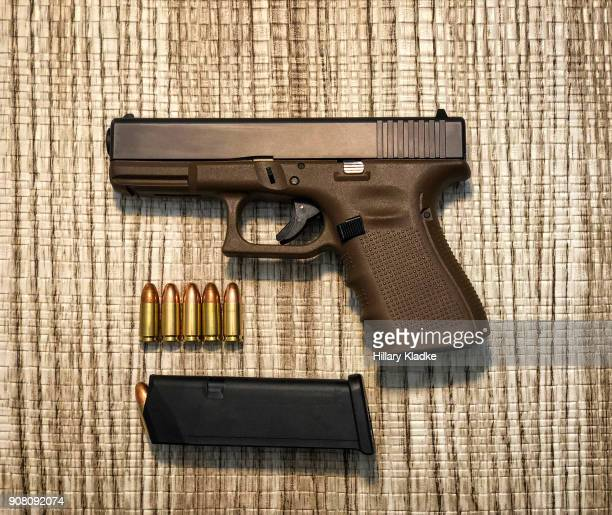 handgun with 9mm bullets - trigger stock photos and pictures