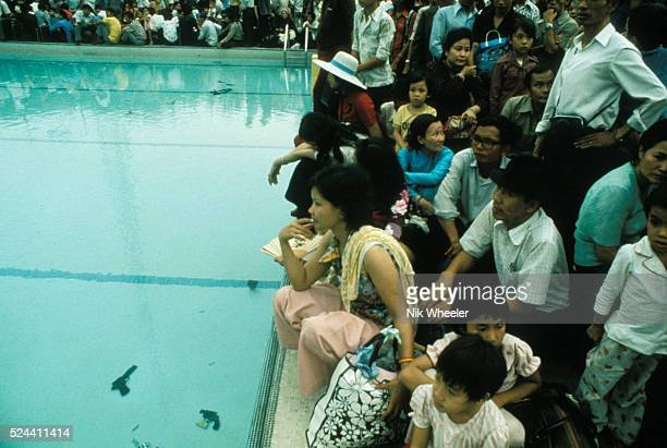 handguns confiscated from refugees trying to escape Saigon lie on the bottom of the US Embassy swimming pool the Vietnamese and Westerners were...