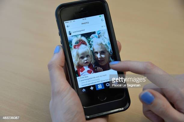 A handheld mobile device displays a tweet from Peaches Geldof showing herself with her mother Paula Yates on April 7 2014 in London United Kingdom...