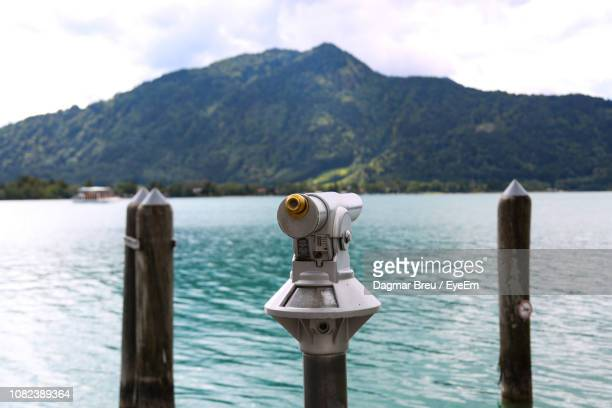 Hand-Held Telescope By Sea Against Mountain