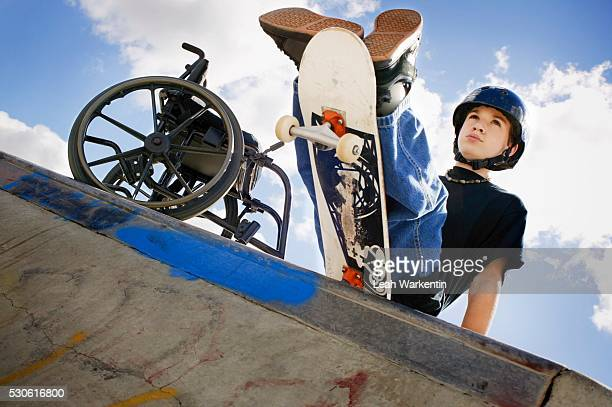 handicapped boy skateboarding in park - schrägansicht stock-fotos und bilder