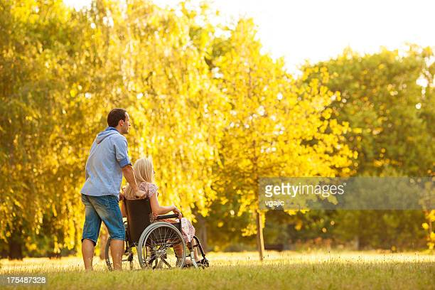 handicapped couple outdoors. - lang haar stockfoto's en -beelden