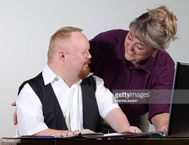 handicapped man and babyboomer at work - down syndrome stock pictures, royalty-free photos & images