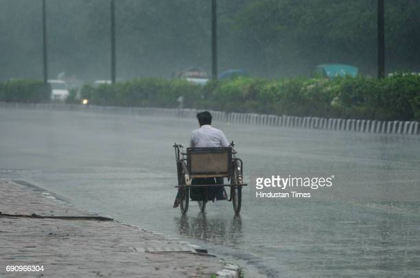 A handicapped person rides his handdriven tricycle amid heavy rains on May 31 2017 in New Delhi India Rains lashed parts of Delhi and NCR at midday...
