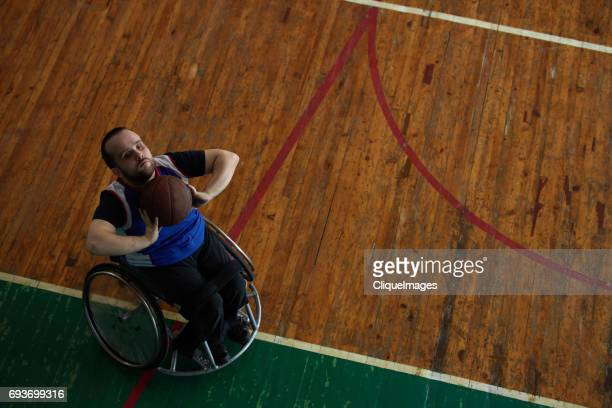 handicapped sportsman throwing ball into basket - cliqueimages stockfoto's en -beelden