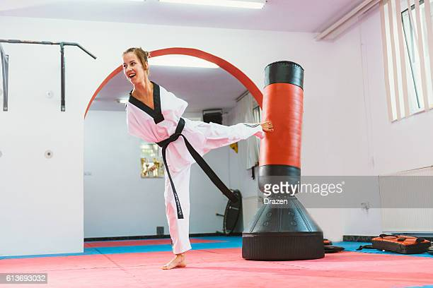 handicapped taekwondo girl kicking back kick - amputee woman stock-fotos und bilder