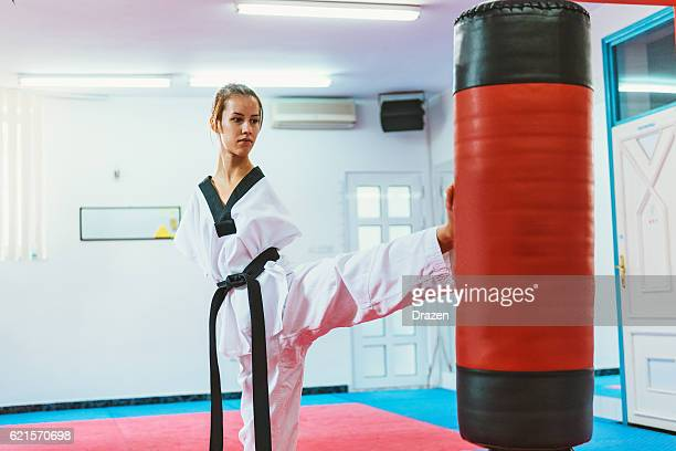 Handicapped taekwondo girl kicking back kick