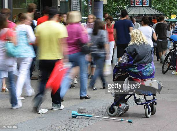 A handicapped woman sits on her walking frame begging for money on August 11 2009 in Berlin Germany Unemployment has risen in Germany with the global...