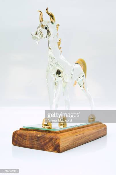 a handicraft glass horse standing on wooden base isolated on whi - bringing home the bacon stock photos and pictures