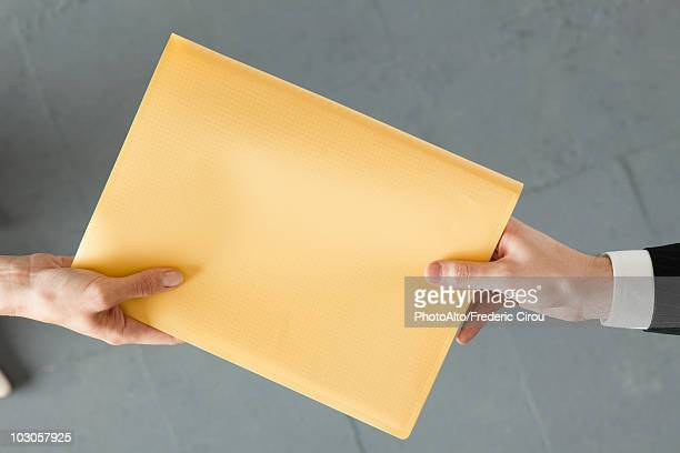 handing colleague large brown envelope - geben stock-fotos und bilder