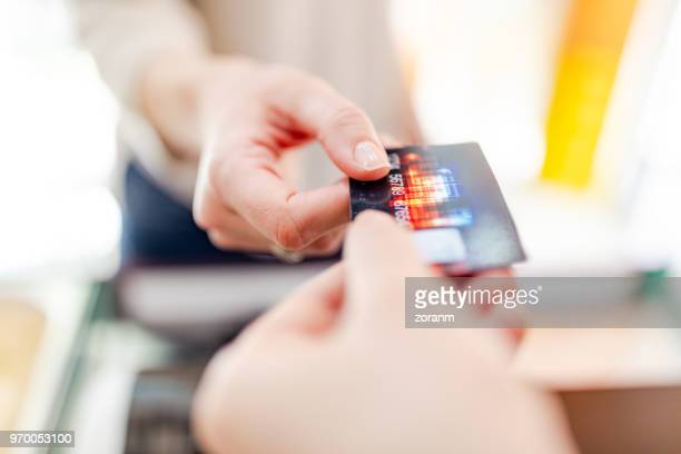 handing credit card to cashier - credit card purchase stock pictures, royalty-free photos & images