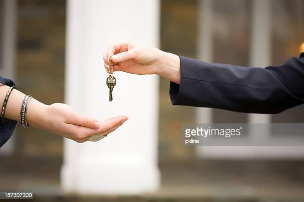 handing keys over in front of house