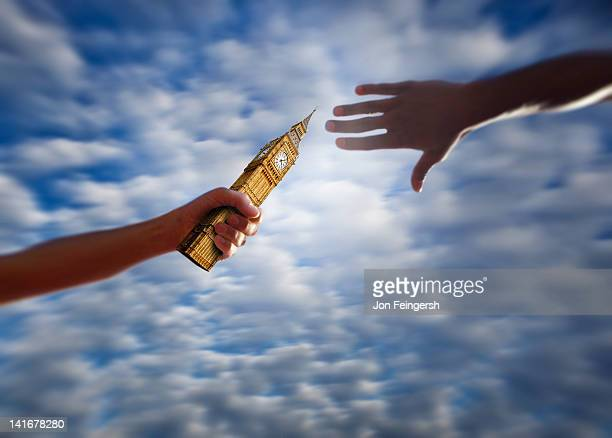handing off baton in relay race - relay stock pictures, royalty-free photos & images