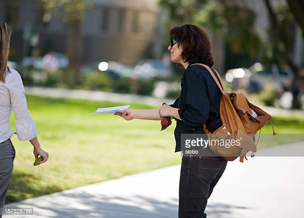 handing out fliers - giving stock photos and pictures