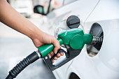 Handle fuel nozzle to refuel the car.