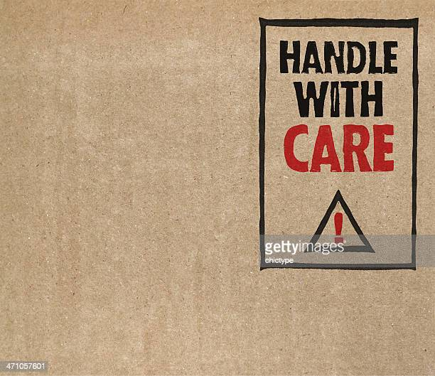 'Handle with care' on brown cardboard