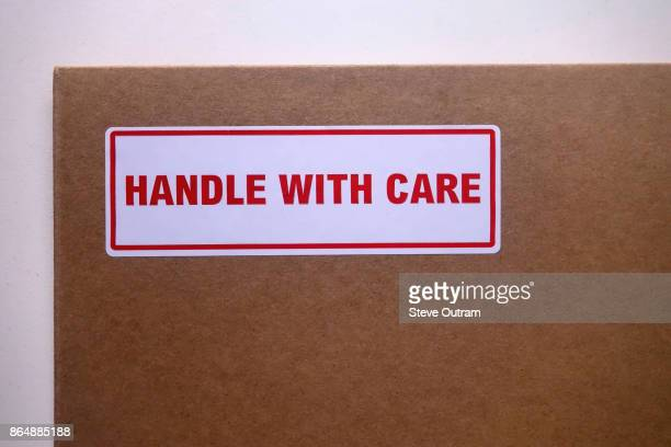 handle with care sticker on cardboard postal packaging - fragile sticker stock pictures, royalty-free photos & images