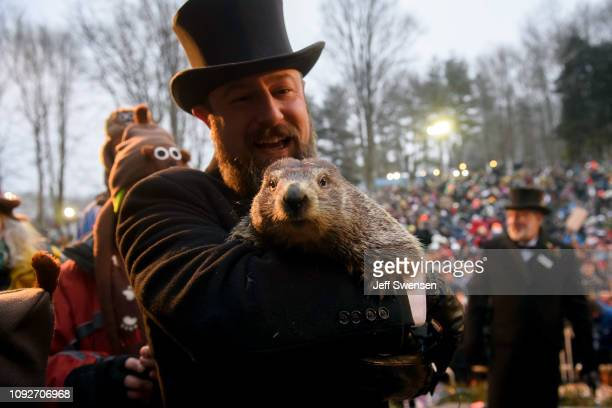 Handler AJ Dereume holds Punxsutawney Phil after he did not see his shadow predicting an early spring during the 133rd annual Groundhog Day...
